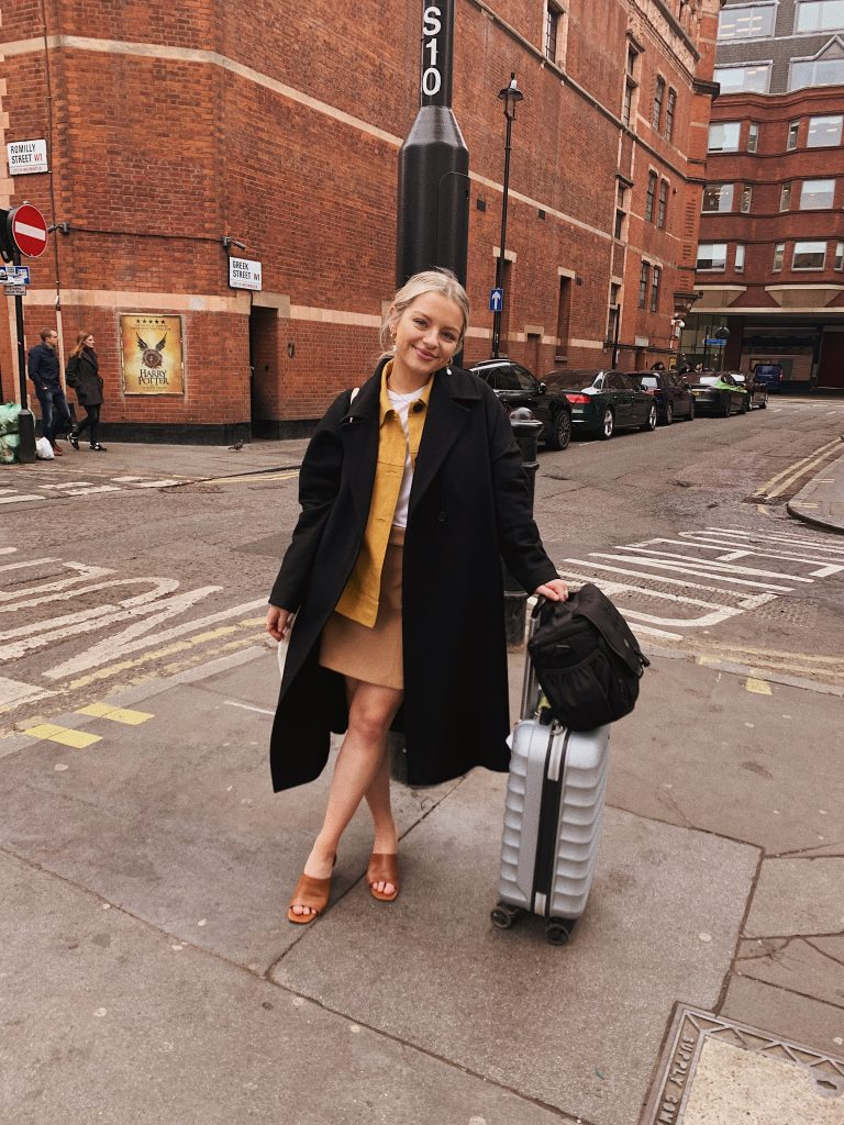 Me standing with suitcase and camera bag on London st. corner
