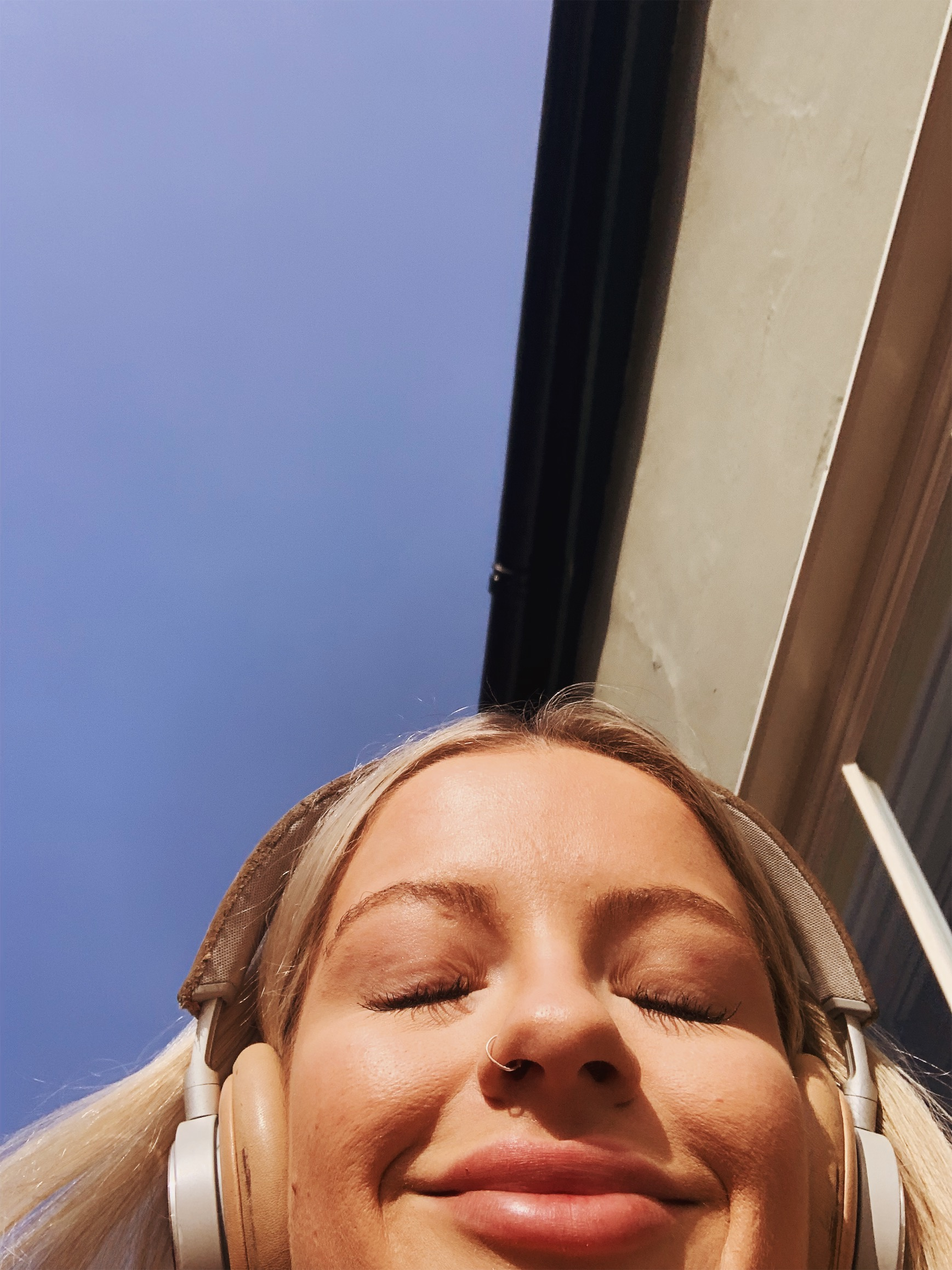 Selfie smiling in sun with headphones on