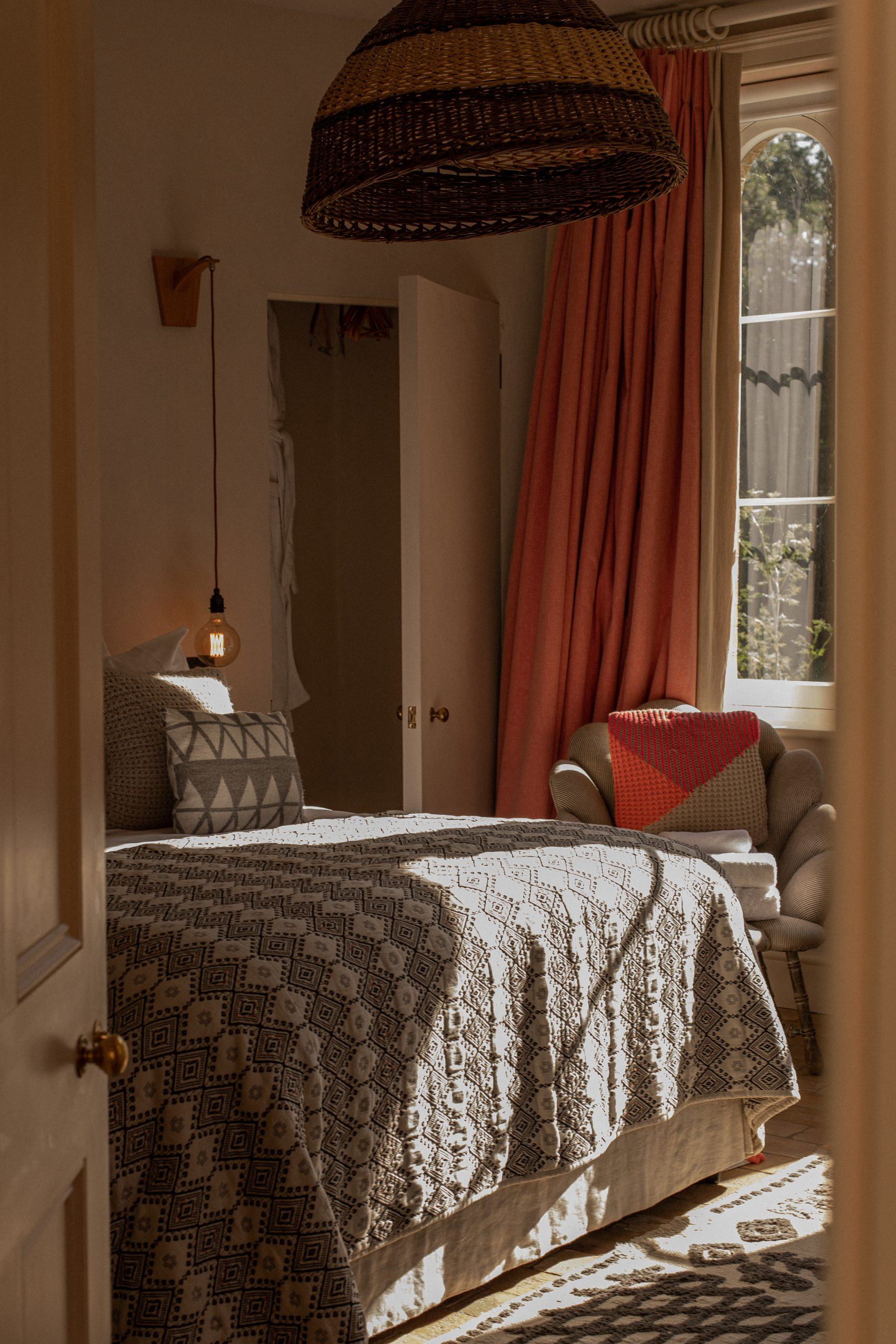 Photo of a bedroom through a doorway. There is a grey throw over the bed, pink hued curtains, an oversized hanging wicker lampshade and plenty of snuggly cushions