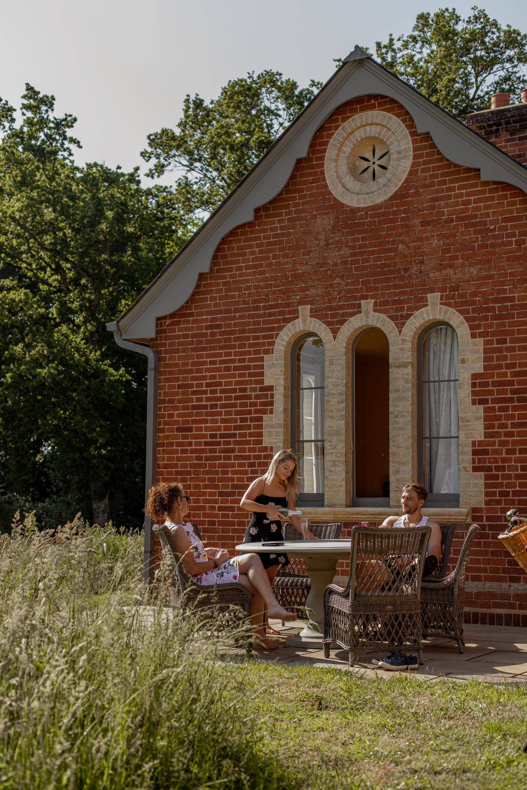 Three people sitting on a round table and wicker chairs outside Garden Cottage, Wilderness Reserve Suffolk. The woman in the middle is pouring wine while the other two speak to each other.