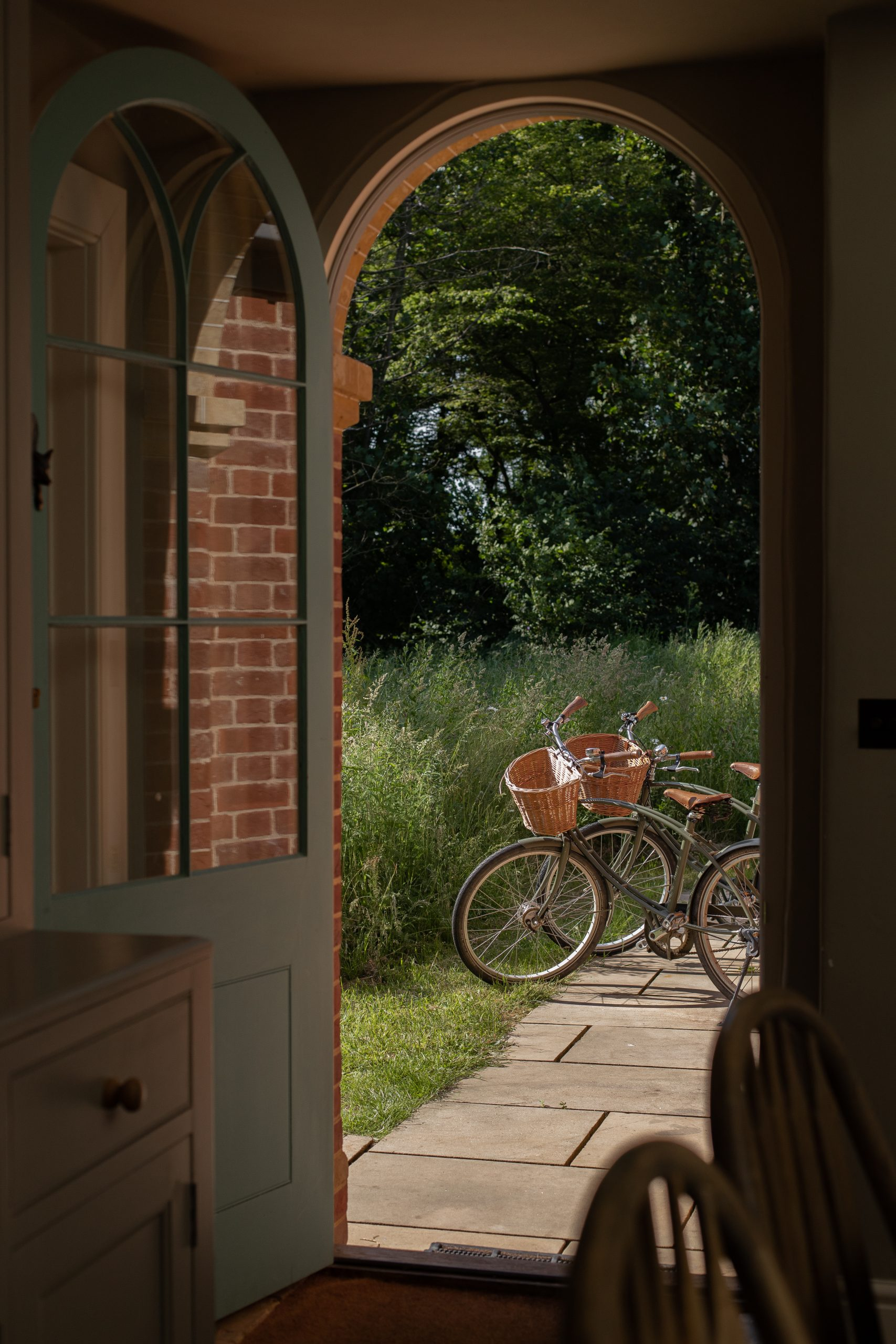 Bicycles through an archway door, looking out onto wild grasses by the Walled Garden Suffolk