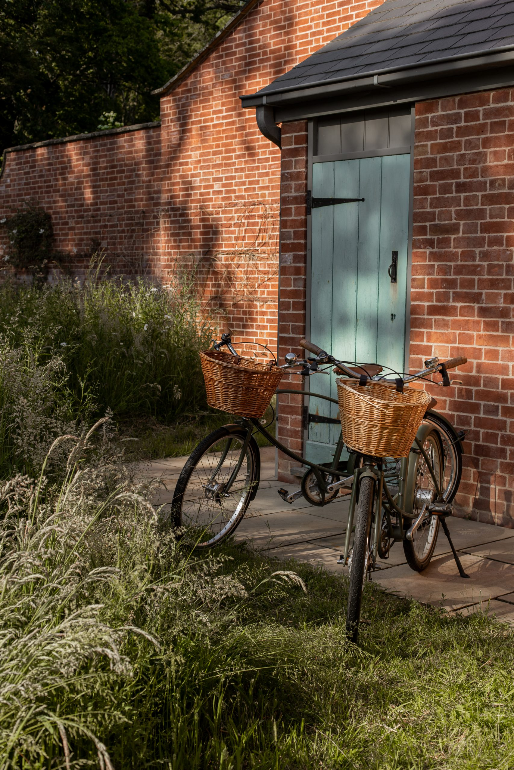 Two bikes standing in the dappled sunglight outside Garden Cottage, Wilderness Reserve Suffolk