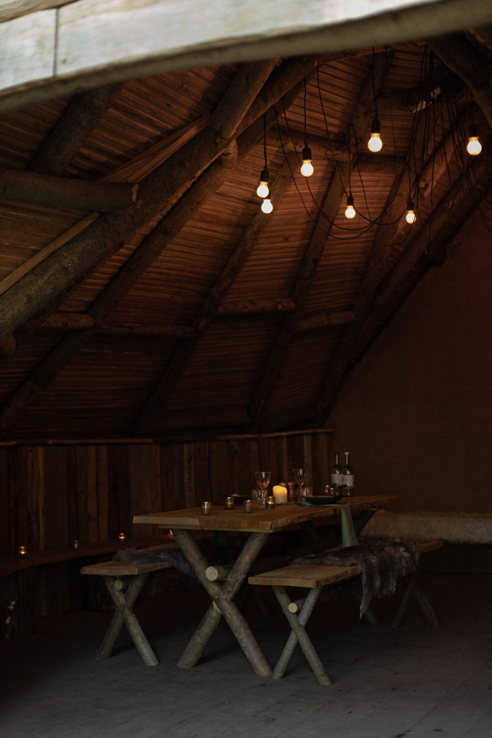 Inside one of the wooden cabins, with bench style seating, fur throws and glowing pendant lights
