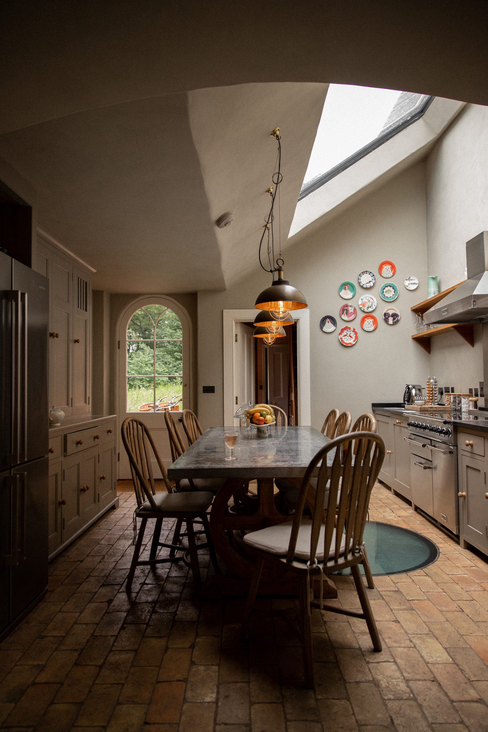 Three hanging pendant lights over the Garden Cottage table. The chair nearest the camera is pulled out and there is a glass of wine on the table