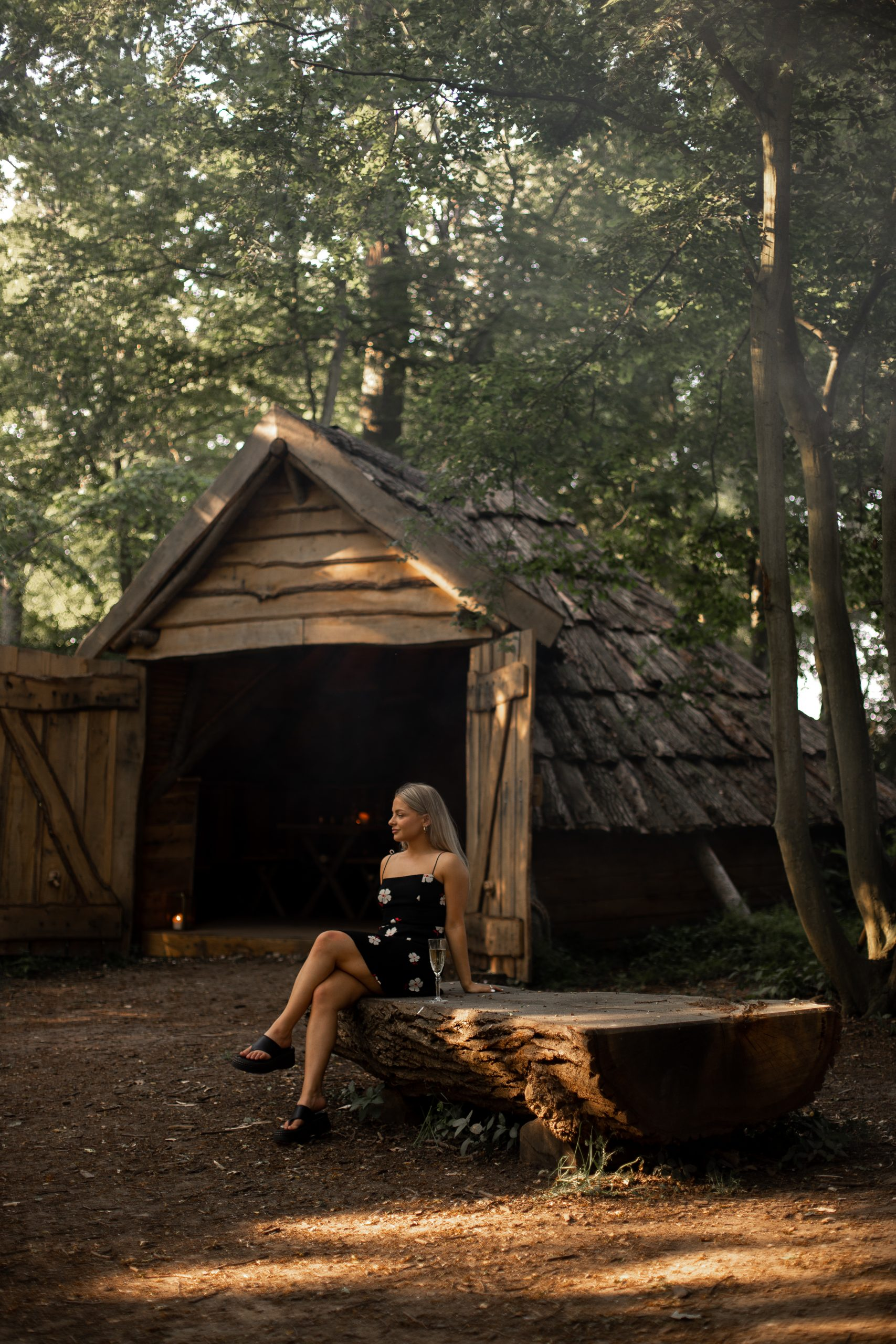 Chloe sitting on a log bench with arms stretched back. There is a wooden cabin in the background
