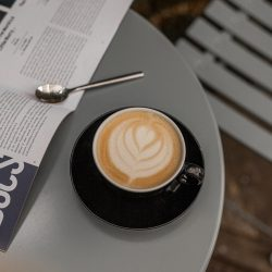 A black coffee cup containing a latte on a light blue table
